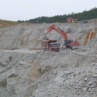 Shovel loading truck in open pit.
